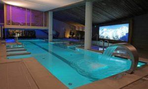 Бетонный бассейн с отделкой плиткой и мозаикой, встроенными гидромассажными зонами и аттракционами